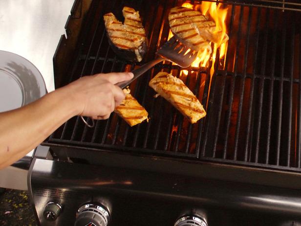 Usar una espatula plana y larga para girar el salmón - Cocinar salmón a la parrilla